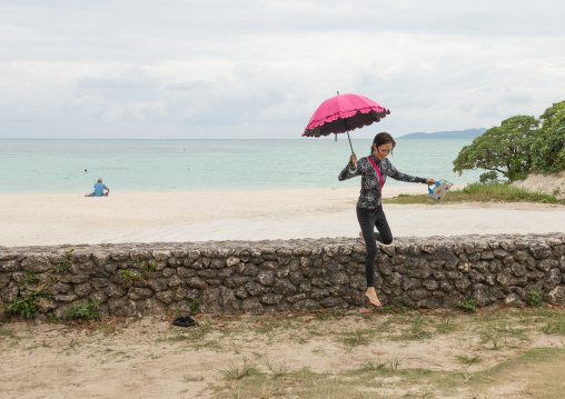 Japanese woman with an umbrella in kondoi beach, Yaeyama Islands, Taketomi island, Japan