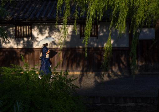 Japanese woman with an umbrella passing in front old houses along the riverbank, Okayama Prefecture, Kurashiki, Japan