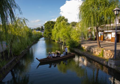 Tourists enjoying a cruise on a small boat on the river in Bikan historical quarter, Okayama Prefecture, Kurashiki, Japan
