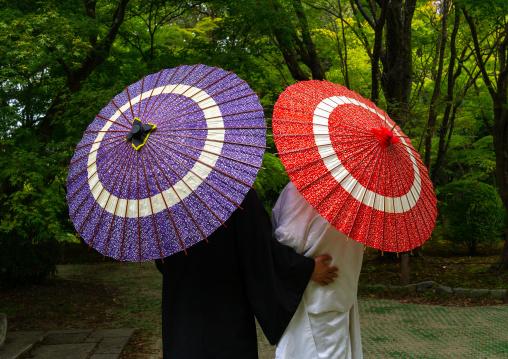Japanese couple with umbrellas in the botanic garden, Kansai region, Kyoto, Japan