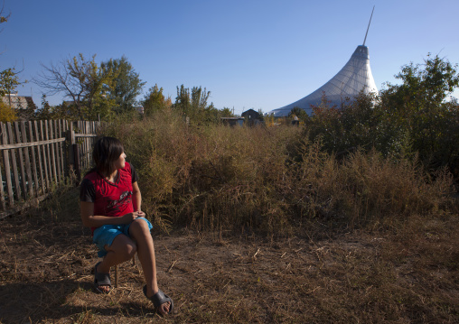 Woman Looking At Khan Shatyr Giant Tent From Her Garden In The Suburbs Of Astana, Kazakhstan