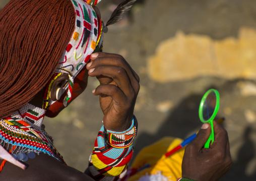 Rendille tribesman applying make up, Turkana lake, Loiyangalani, Kenya