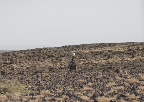 Turkana woman carrying a bag on her head and crossing an arid area, Turkana lake, Loiyangalani, Kenya