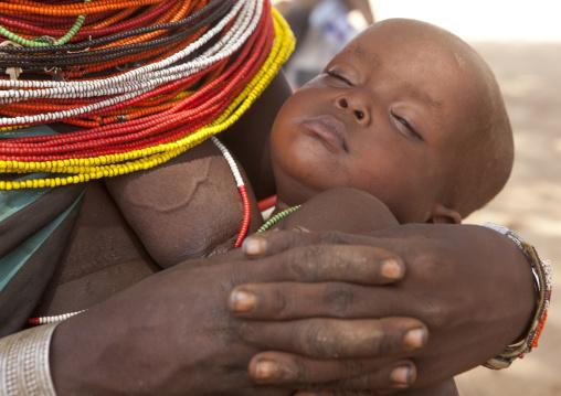 Rendille tribeswoman holding her sleeping baby, Marsabit district, Ngurunit, Kenya