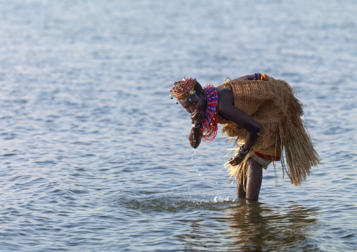 El Molo tribe woman drinking in the lake, Rift Valley Province, Turkana lake, Kenya