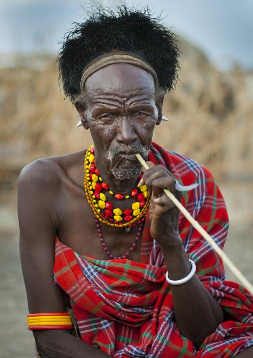 Turkana tribesman using a big toothbrush, Turkana lake, Loiyangalani, Kenya