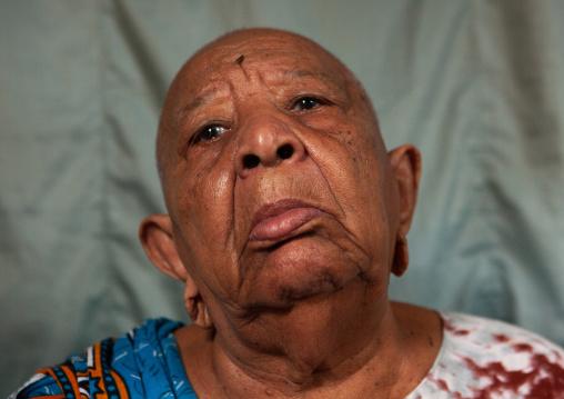 Portrait of a senior woman with shaved head and enlarged earlobes, Lamu County, Siyu, Kenya