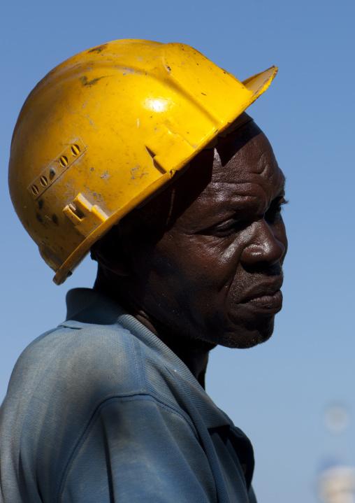 Kenyan worker wearing a yellow helmet, Lamu County, Lamu, Kenya