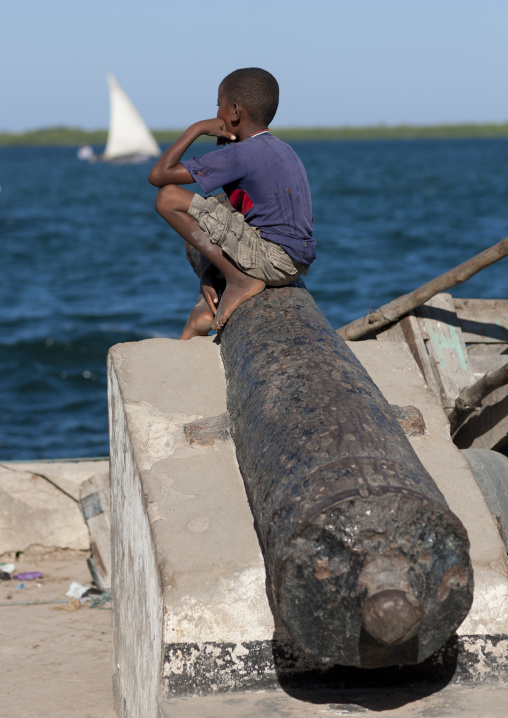Boy sit on a cannon along a dockside, Lamu County, Lamu, Kenya