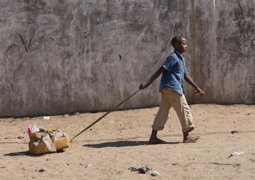 Little boy dragging a toy in a sandy street, Lamu County, Lamu, Kenya