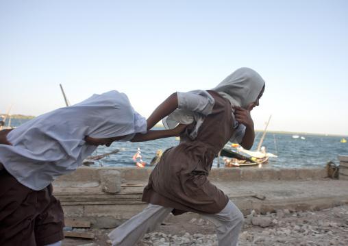 Two schoolgirl teenagers running alongside the dock, Lamu County, Lamu, Kenya