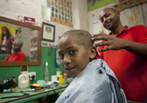 Young boy getting head shaved in barbershop, Lamu County, Lamu, Kenya