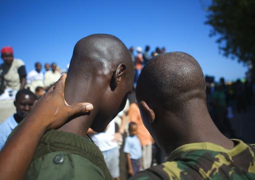 Two policemen holding each other in the street, Lamu County, Lamu, Kenya