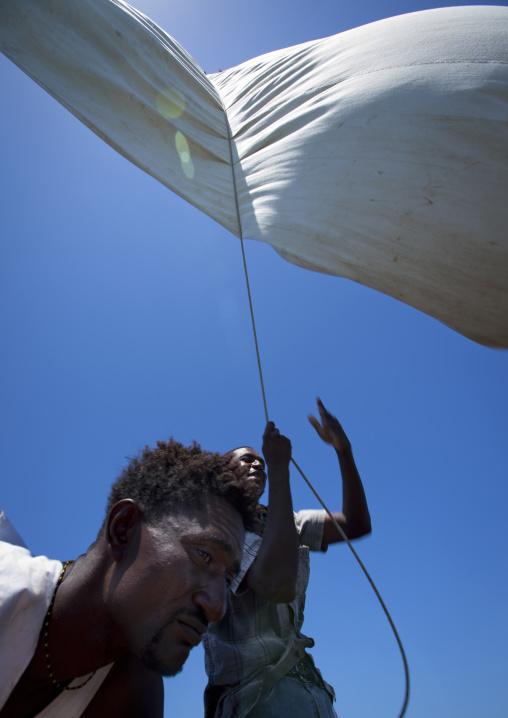 Man raising the sail on a dhow, Lamu County, Lamu, Kenya