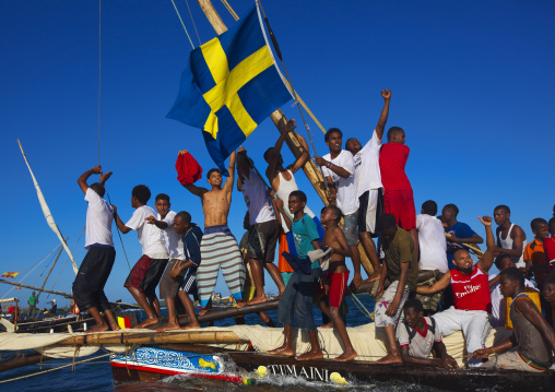 Swedish flagged dhow with crew cheering themselves during the Maulid festival race, Lamu County, Lamu, Kenya