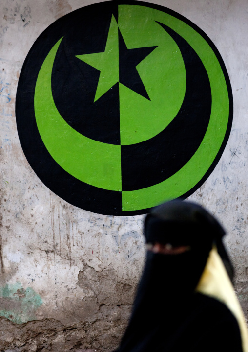 Muslim woman in niqab passing by a muslim crescent and star sign in the street, Lamu County, Lamu, Kenya