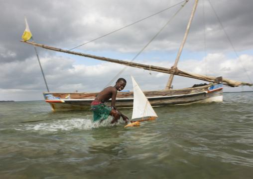 Young boy playing with dhow model along seashore, Lamu County, Lamu, Kenya