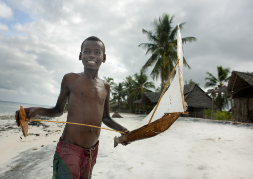 Young boy playing with a dhow boat model, Lamu County, Lamu, Kenya