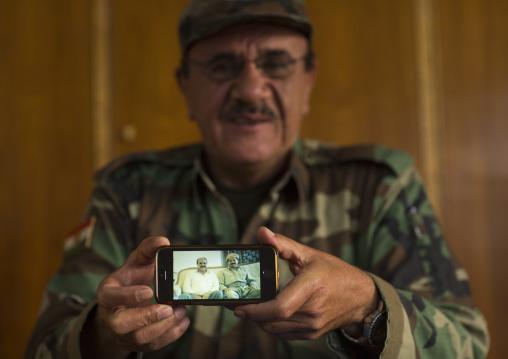 Kurdish General Peshmerga On The Frontline Showing A Picture Of Himself With President Massoud Barzani, Duhok, Kurdistan, Iraq