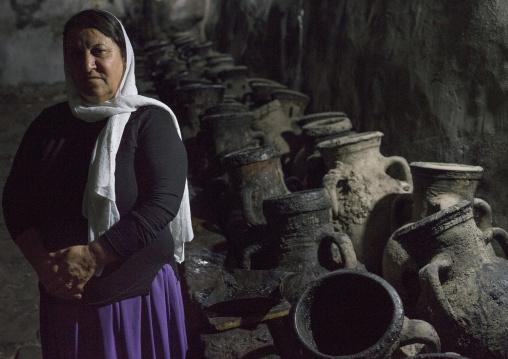 Yazidi Woman Standing In Front Of Olive Oil Jars, Temple City Of Lalesh, Kurdistan, Iraq