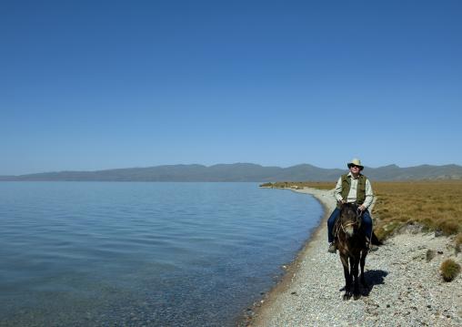 Western Man Riding A Horse On The Shores Of Song Kol Lake, Jaman Echki Jailoo Village, Kyrgyzstan