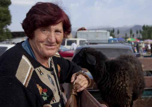 Old Woman With A Sheep In The Storage Compartment Of Her Truck, Kochkor Animal Market, Kyrgyzstan