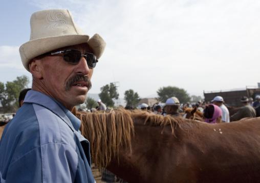 Man Wearing A Kalpak Hat And Sunglasses At The Animal Market Of Kochkor, Kyrgyzstan