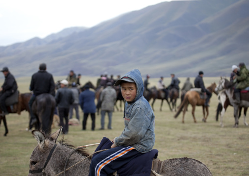Young Boy With Cap Riding A Donkey In The Middle Of Adults Riding Horses, Saralasaz Jailoo, Kyrgyzstan
