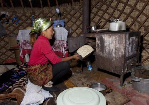 Woman With Headscarf Baking Food In An Oven Inside Her Hut, Jaman Echki Jailoo Village, Kyrgyzstan