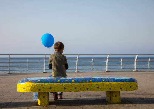 Boy sit on a bench with a balloon in the corniche, Beirut Governorate, Beirut, Lebanon