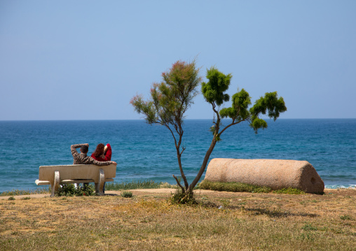 Couple sits on a bench in front of the sea, South Governorate, Tyre, Lebanon