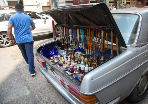 A man selling prayer beads and souvenir from the trunk of his car in the street, Beirut Governorate, Beirut, Lebanon