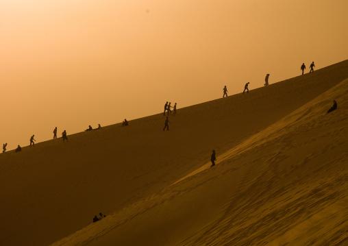 People in the desert on a dune, Tripolitania, Ghadames, Libya