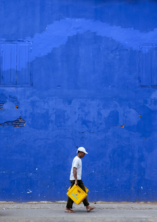 Man in front of a blue wall, Pakse, Laos
