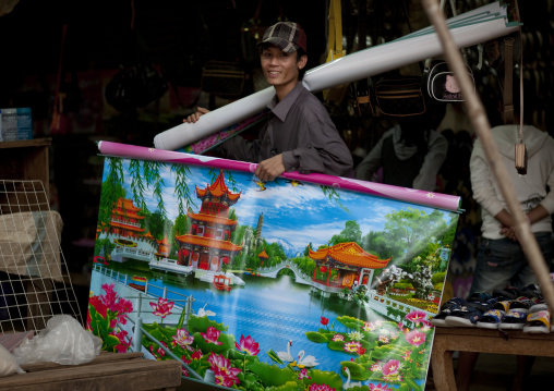 Man selling a chinese poster on a market, Phonsaad, Laos