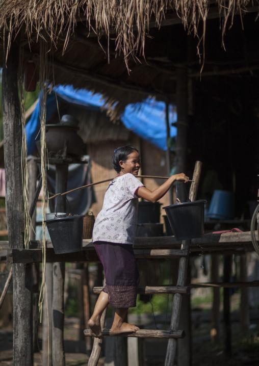 Bru minority woman carrying water in her house, Phonsaad, Laos