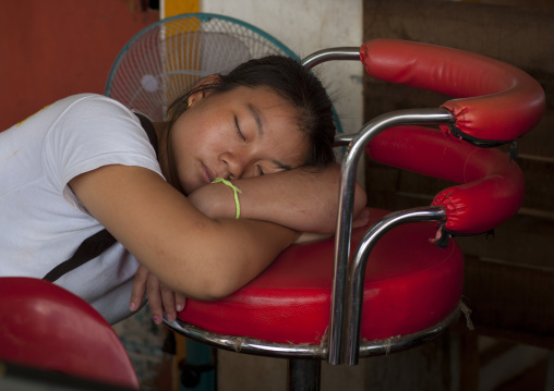Woman sleeping on a chair, Pakse, Laos