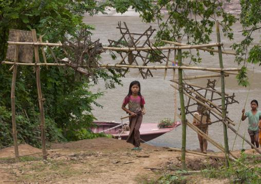 Khmu minority girl passing under the traditional gate, Xieng khouang, Laos