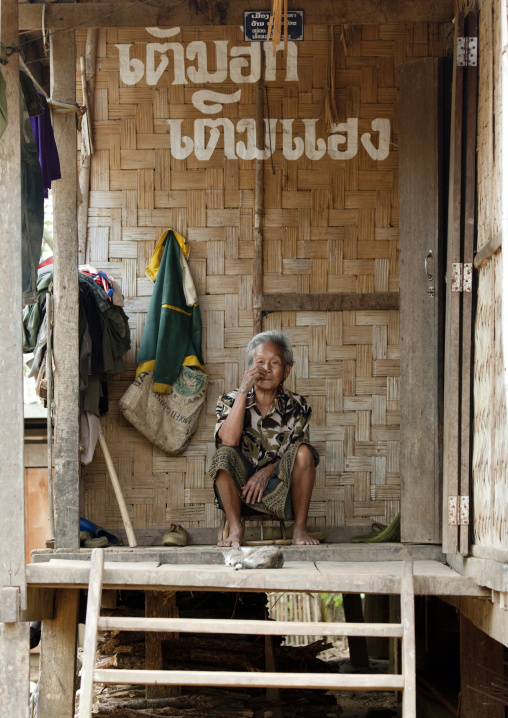 Khmu minority man sitting in front of his house, Xieng khouang, Laos