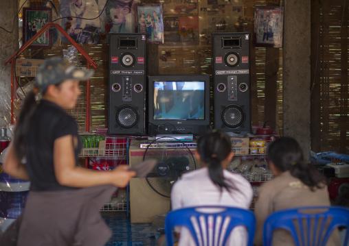 Lao lum teenagers watching television, Pakbeng, Laos