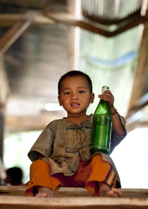 Akha minority boy holding a beer bottle, Ban ta mi, Laos