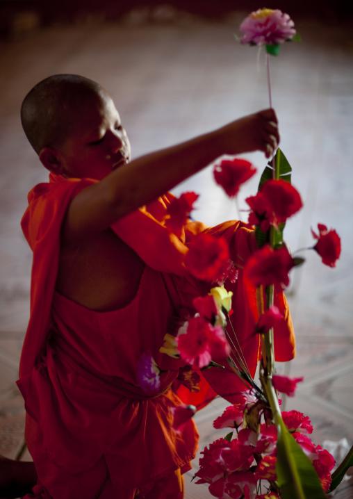 Novice buddhist monk arranging flowers, Nam deng, Laos