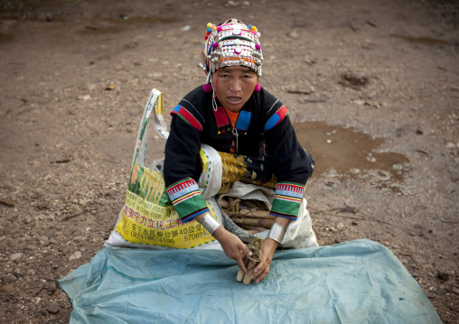 Akha minority woman with traditional headdress in a market, Muang sing, Laos