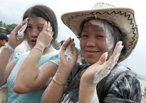 Girls with flour on the face during pii mai lao new year celebration, Luang prabang, Laos