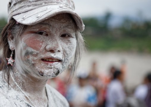 Woman with flour on the face during pii mai lao new year celebration, Luang prabang, Laos