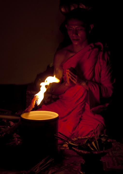 Monk praying in front of a fire, Luang prabang, Laos