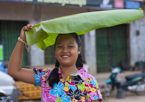 Hmong minority woman protecting herself from the rain with a banana leaf, Luang prabang, Laos