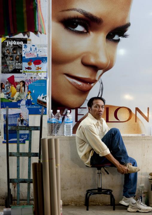 Man in front of a revlon advertisement, Vientiane, Laos