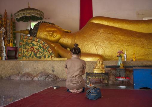 Man praying in front of lying buddha in pha bat monastery, Pakse, Laos