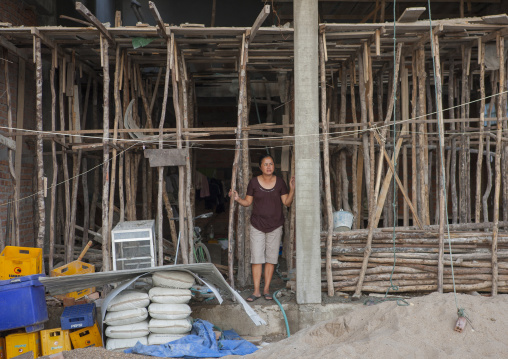 Women in front of her house in construction, Thakhek, Laos